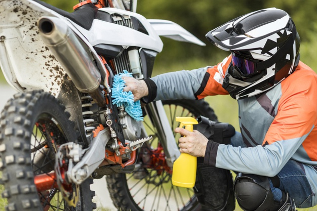 active-man-cleaning-motorbike-outdoors_23-2148585536
