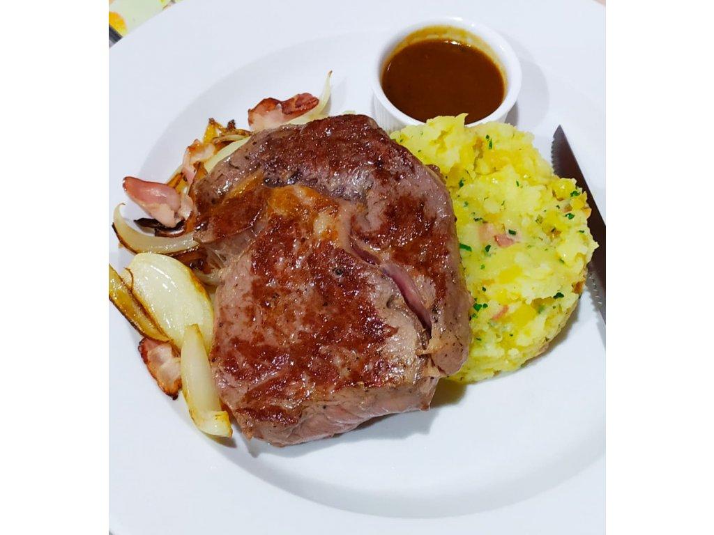 300g Steak z hovězí roštěné s opečenou cibulkou, slaninou, šťouchané brambory