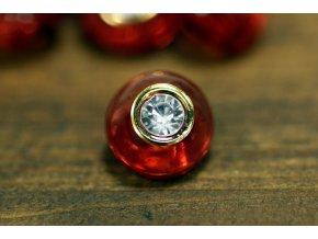 Červený knoflík s čirým, broušeným středem