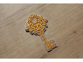 Šedo-žlutá aplikace ve tvaru klíče