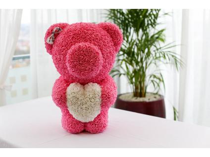 Růžový stojící medvídek z růží s bílým srdcem