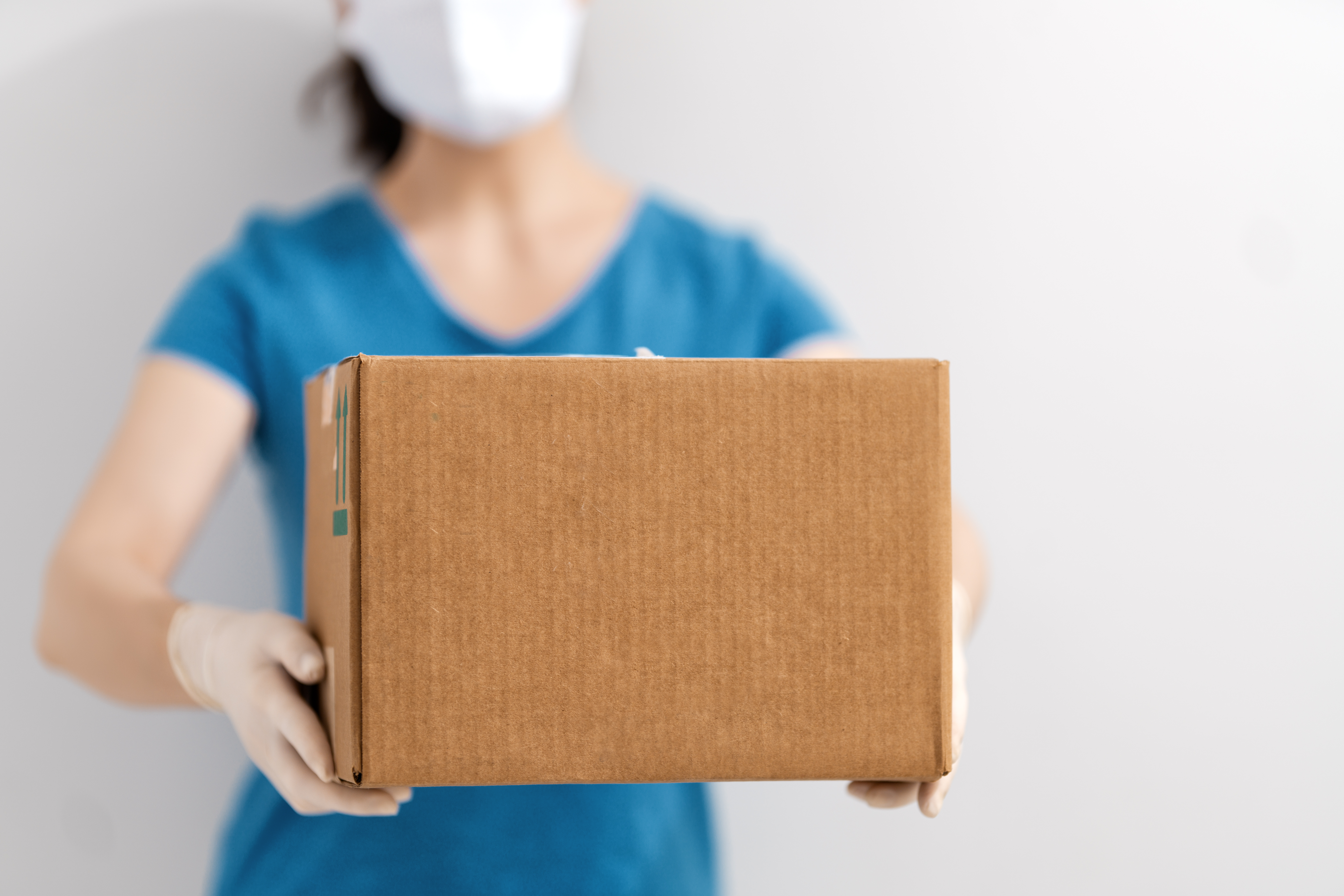 delivery-woman-holding-cardboard-box-EB7RAC3