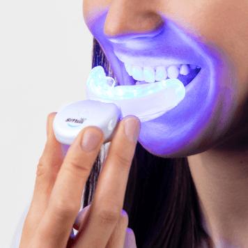 žena si nasazuje náústek pro bělení zubů