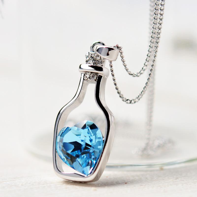 Náhrdelník ve tvaru lahvičky s modrým kamínkem ve tvaru srdce uvnitř.