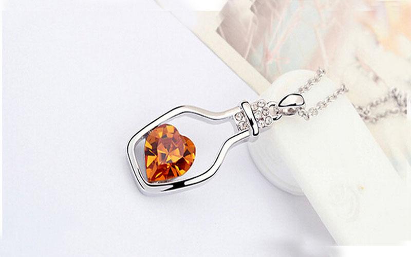Náhrdelník ve tvaru lahvičky s žlutým kamínkem ve tvaru srdce uvnitř.