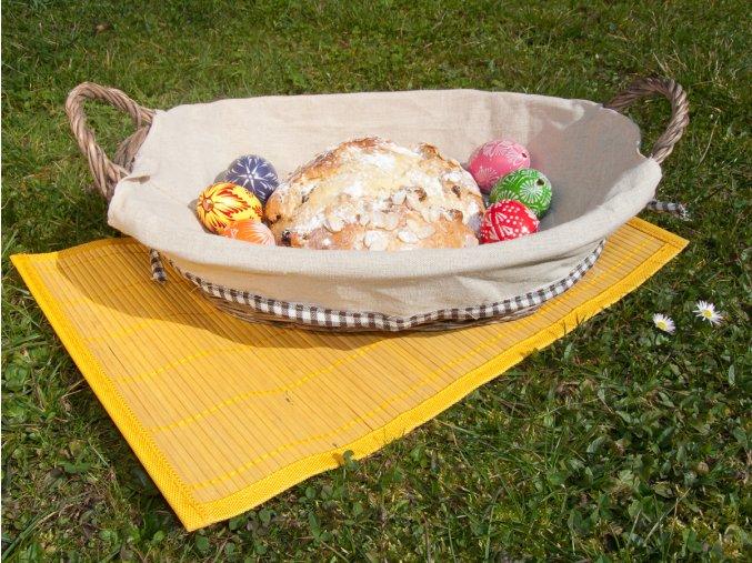 Proutěná šedá ošatka Vingo s uchy a s látkou obšitou kostkovanou stuhou na bambusovém prostírání Vingo žluté barvy doplněno o dekorace vajíček a velikonočního mazance