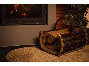 Vingo proutěný koš na dřevo s pytlovinou postavený u krbu ve večerních hodinách.