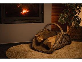 Vingo ratanový koš na dřevo s pytlovinou stojící na přírodní rohoži u hořícího krbu.