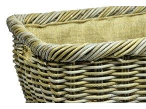 Vingo ratanový úložný koš hranatý v zemitých barvách postavený na přírodní rohoži u krbu ve večerních hodinách.