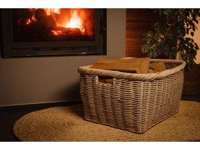Vingo velký bílý ratanový koš s jutou vyskládaný dřevem stojí u hořícího krbu ve večerní atmosféře.