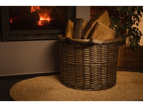 Vingo nůše šedá (koš dvojuchý) vyrobený z obarveného proutí stojící u krbu s naskládaným dřevem při večerní atmosféře.