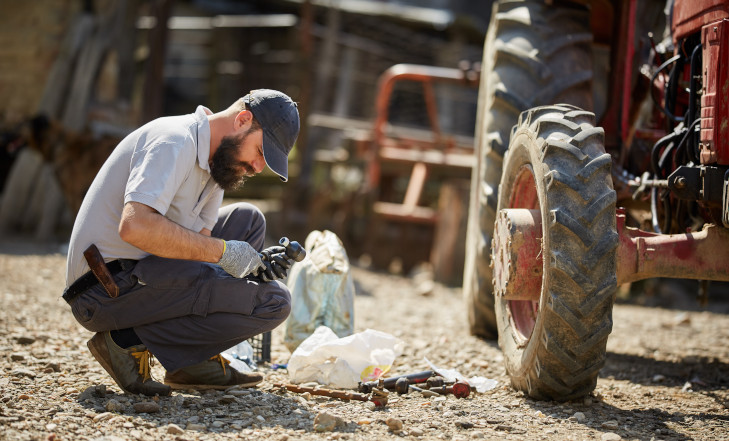 Traktorista opravuje traktor, nářadí