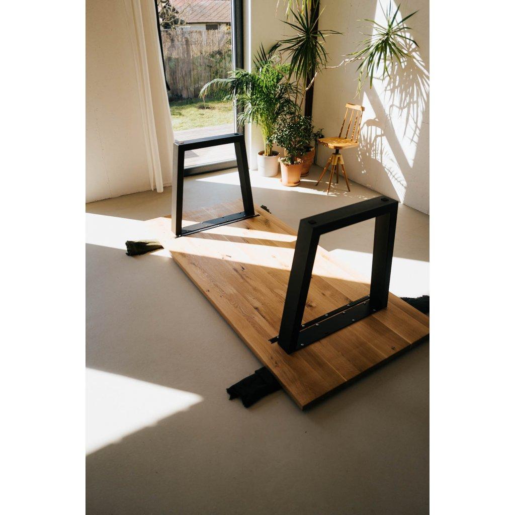 dřevěný jídelní stůl s kovovým podnožím na tmavé podlaze