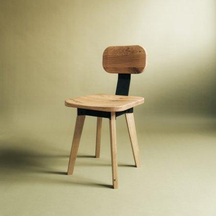 Jídelní židle z masivu na zeleném pozadí