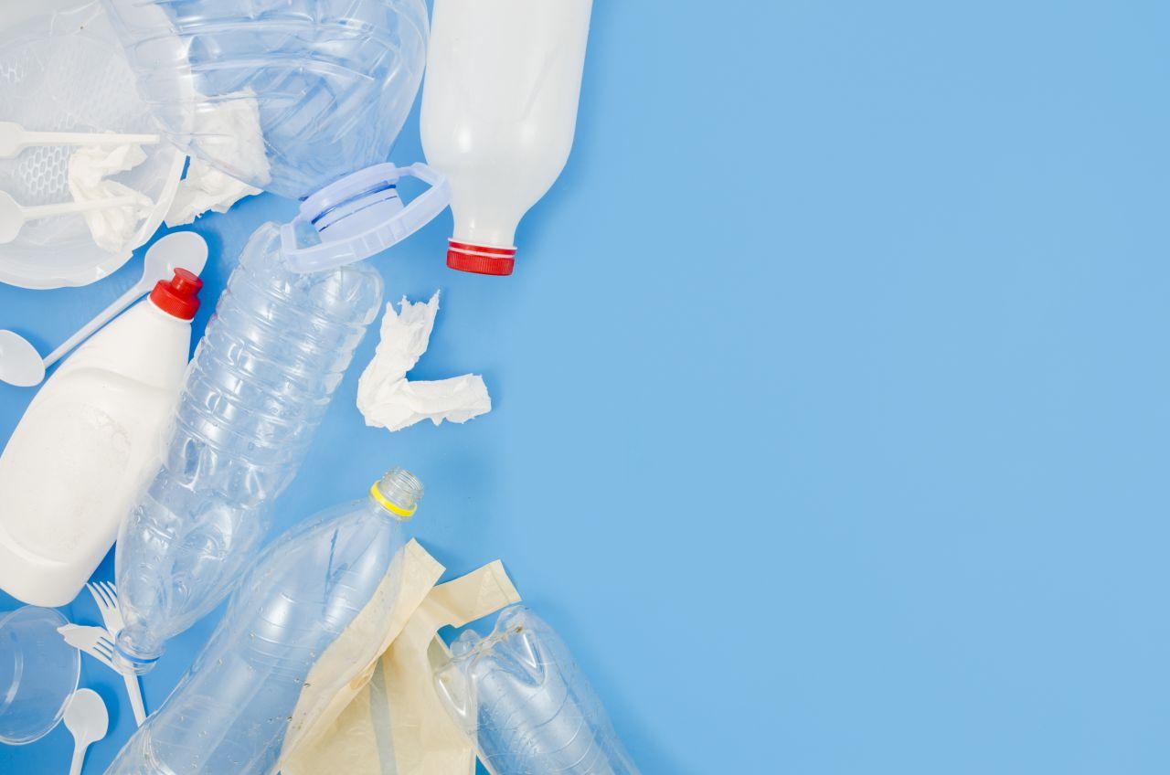 waste-plastic-trash-crumpled-paper-blue-background