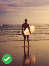 Surfař v západu slunce na pláži